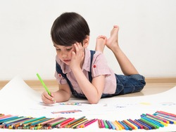 small boy draws while lying on the floor.