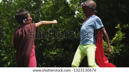 Small boy dressed as superhero punching toward older boy also dressed as superhero #1323130676
