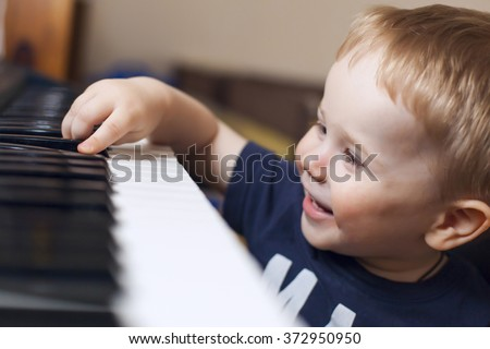 Small boy enjoys playing electric piano  (synthesizer) for the first time #372950950