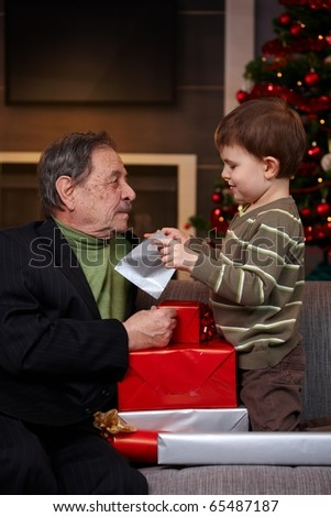 Small boy getting christmas present from grandfather, looking into bag. ?