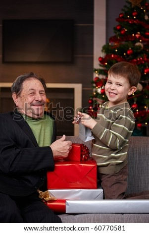 Small boy giving christmas present to happy grandfather, smiling. ?
