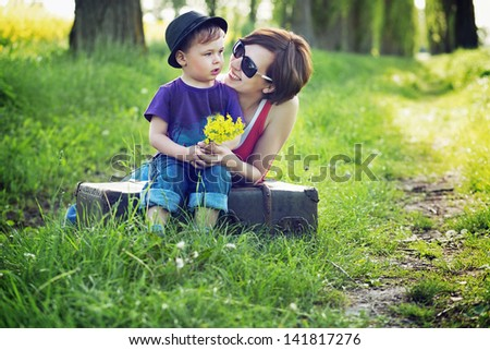 Small boy giving his mom flowers