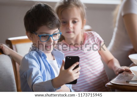 Small boy holding smartphone making picture or playing game, curious little girl looking at video on phone shown by brother, cute kids having fun watching cartoon on mobile during breakfast in kitchen