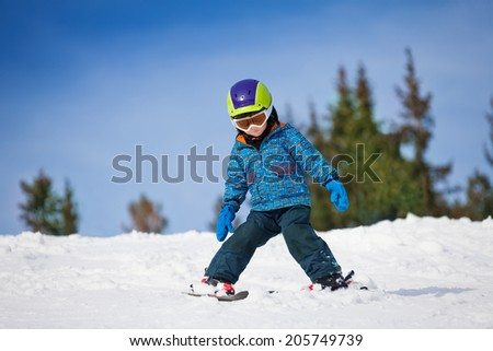 Small boy in ski mask and helmet learns skiing