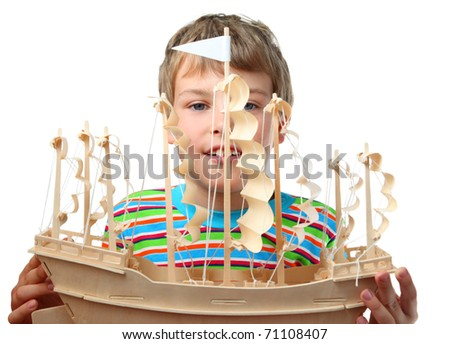 Small boy in striped shirt holds artificial wooden ship with paper sails