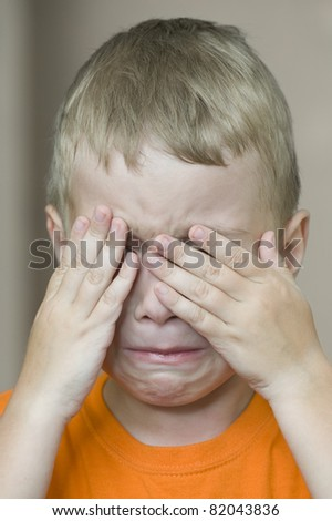 Small boy is covering his face by hands
