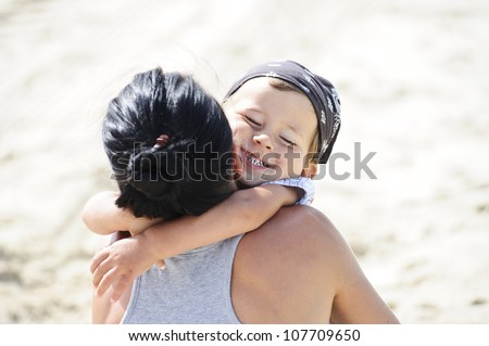 Small boy is hugging his mom on the beach.