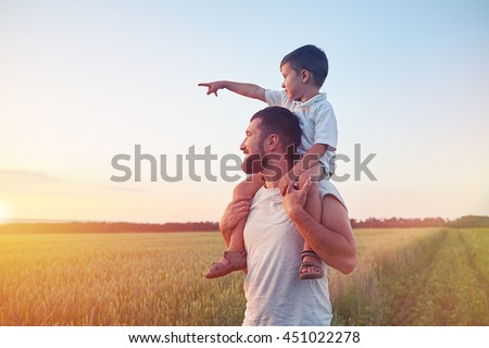 Small boy is sitting on his father??s shoulders and pointing at the sun in the field during beautiful sunset