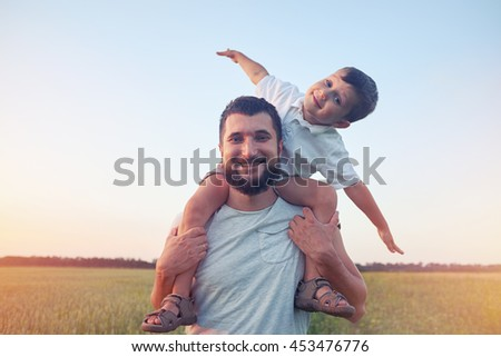 Small boy is sitting on his father's shoulders and pretending a plane during walk in the field #453476776