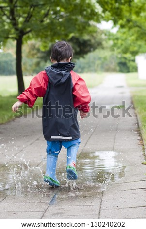 Small boy jumping in a puddle on the path in a park after a rain.