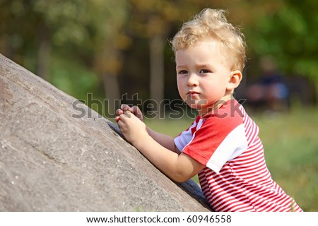 Small boy leaning on a rock in the park