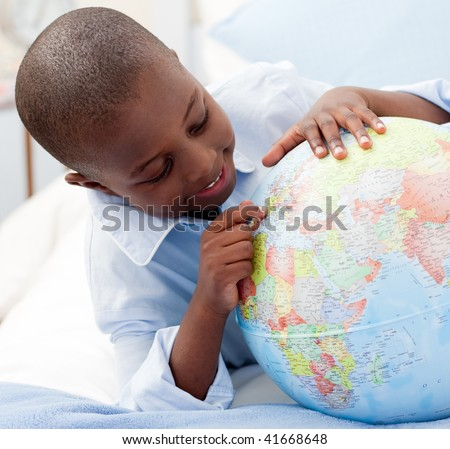 Small boy looking at a Globe in his bedroom