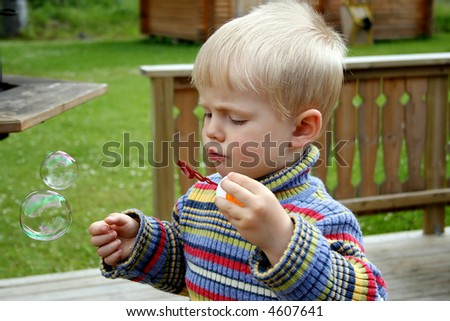 Small boy making soap bubbles outdoor at spring weather - stock photo