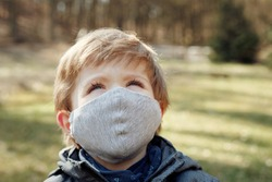 Small boy outside during a pandemic, wearing fabric facemask, looking at the sky, detail