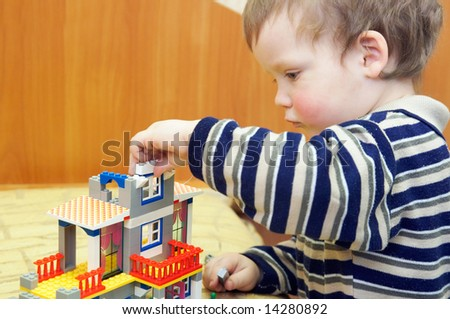 Small boy play with building set for children (built a house)
