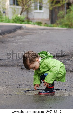 small boy playing in puddles
