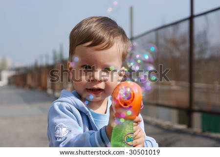 small boy playing with soap bubbles gun
