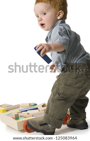 Small boy playing with toy in front of white background