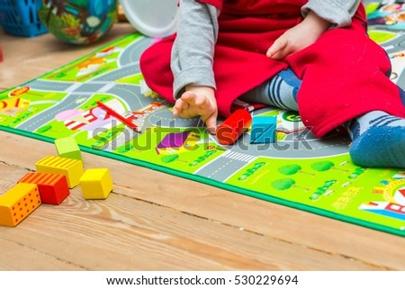 Small boy playing with wooden blocks on floor. Baby toy and child. #530229694