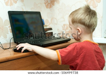 small boy plays on computer