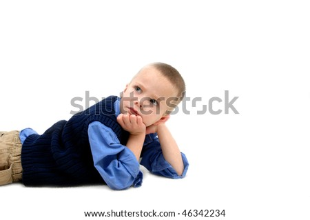 Small boy puts chin in hand and ponders over his childhood concerns.  He is laying in an all white room and room is left for personalization. - stock photo