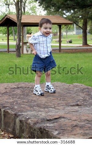 Small Boy Standing On Large Rock Pulling Up His Shorts At ...