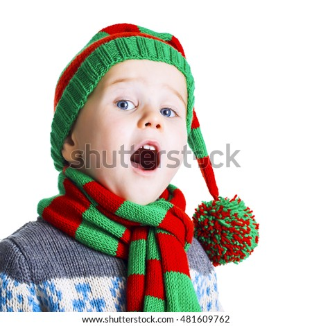 Small boy with blue eyes in knitted hat, scarf and sweater sings a Christmas song. Isolated on white background.  #481609762