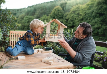 Small boy with senior grandfather in wheelchair constructing birdhouse, diy project. Stockfoto ©