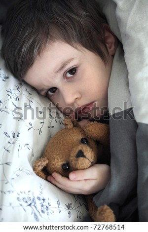 Small boy with teddy bear toy in the bed