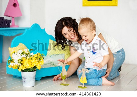 Small boy 2-3 years blond hair sitting on the floor with his young mother. They play an easter bunny and laughing. Around them bright decor: light green pillow, turquoise table. #414361420
