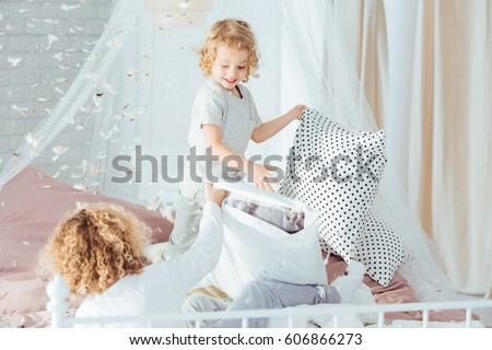 Small boys having pillow fight, doing mess in room