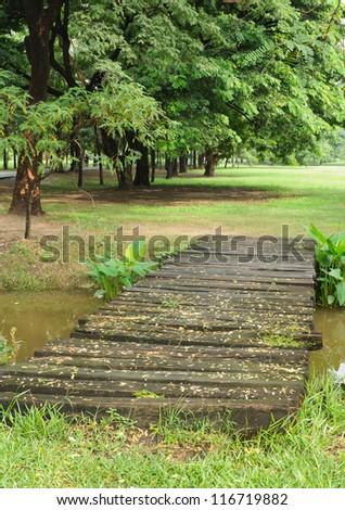 Small bridge across a stream in the park - stock photo