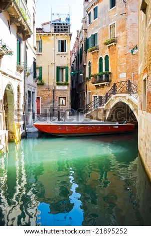 Small bridge over blue and green water of a venetian canal, Italy