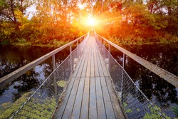 Small bridge over river in forest on sunset background
