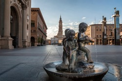 Small bronze fountain located in the plaza de El Pilar de Zaragoza, with the tower of the cathedral of La Seo in the background.