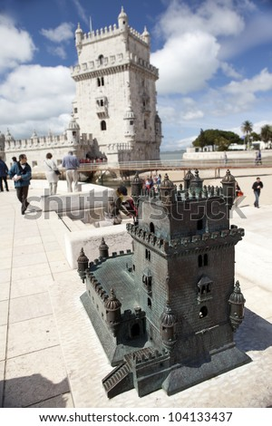 Small bronze scale model of the Belem Tower in Lisbon, Portugal. Actual tower is on the background.