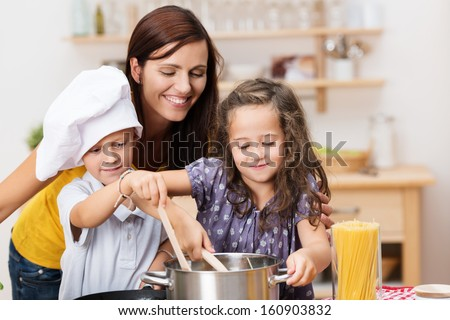 Small brother and sister cooking a meal both stirring the contents of the same pot watched over by their laughing young mother