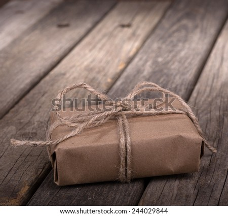 Small brown package wrapped with string on old wood boards