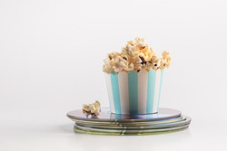Small bucket of popcorn placed on a stack of movie DVDs. A concept for home theater entertainment.