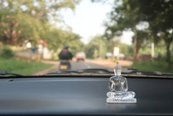 Small Buddha image on the SriLankan taxi dashboard console show respect to the Lord Buddha (to protect the vehicle from danger or to prevent a crash or accident)