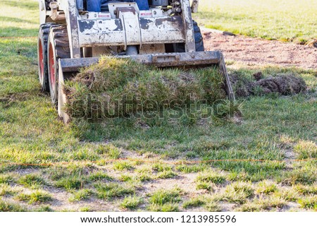 Small Bulldozer Removing Grass From Yard Preparing For Pool Installation