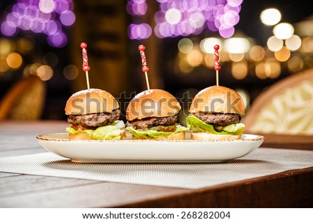 Small burgers served on one plate as appetizers
