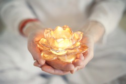 Small burning candle in an transparent orange lotus shaped glass candle holder laying on streched woman's hands with  soft-focused white women clothes in the background