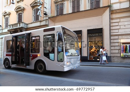small bus goes on streets of Rome, Italy, old beautiful houses