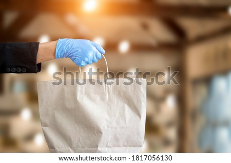 Small business and service concept with young woman Wearing blue gloves Filed paper bag with take away drink in cafe Foto d'archivio ©