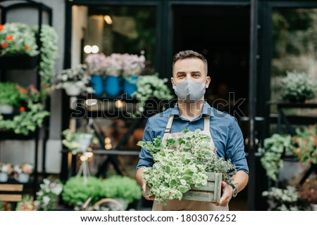 Small business and start of working day. Man in protective mask takes out box of plants outside in front of flower shop