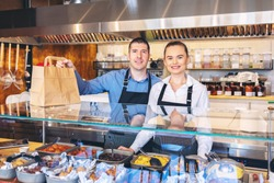 Small business and to go service concept due to isolation emergency with young restaurant owners working hard for take away food orders and deliveries to clients staying at home in quarantine