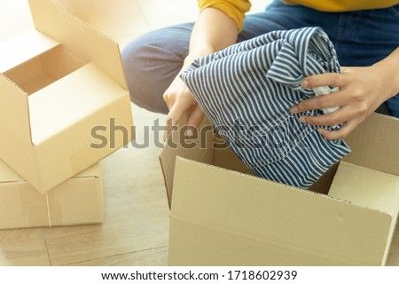 Small business concept : young woman start up small business owner packing cloth in the box at home, freelance seller prepare product for packaging process at shop.