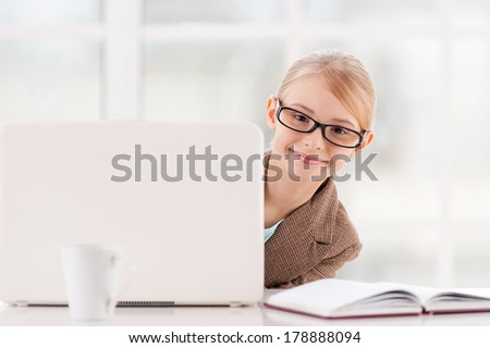 Small business. Cute little girl in glasses and formalwear looking out of the laptop and smiling while sitting at the table