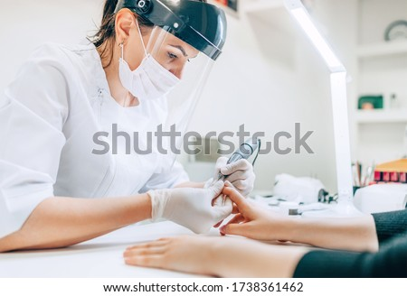 Small business existence at COVID-19 lockdown concept. Professional manicure master in Transparent Safety Face Shield using Electric Nail Polisher Tool for Glazing treatment manicure procedure.  Stok fotoğraf ©